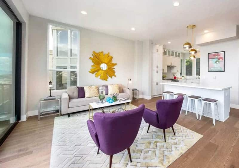 Living room with purple mid century modern chair, yellow wall mirror, area rug and beige couch