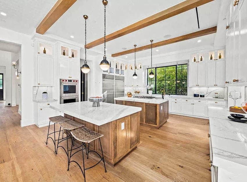 Modern farmhouse kitchen with two islands with wood cabinets pendant lights and white main cabinetry