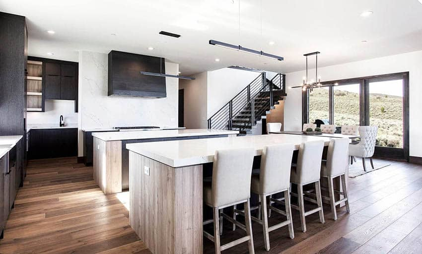 Modern kitchen with 2 islands white quartz countertops light brown cabinets and black main cabinets