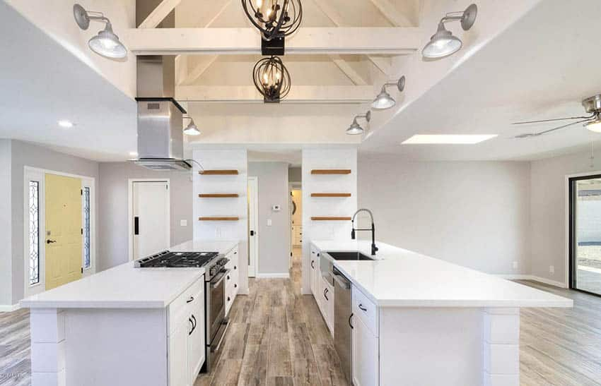 Modern kitchen with double islands with white cabinets vaulted ceiling