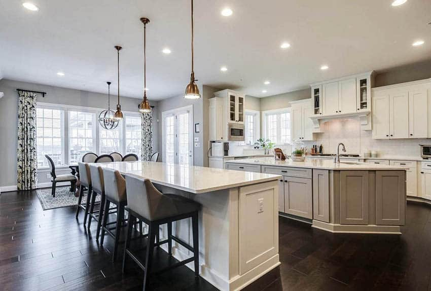 Open concept kitchen with double islands breakfast bar and center sink white cabinets