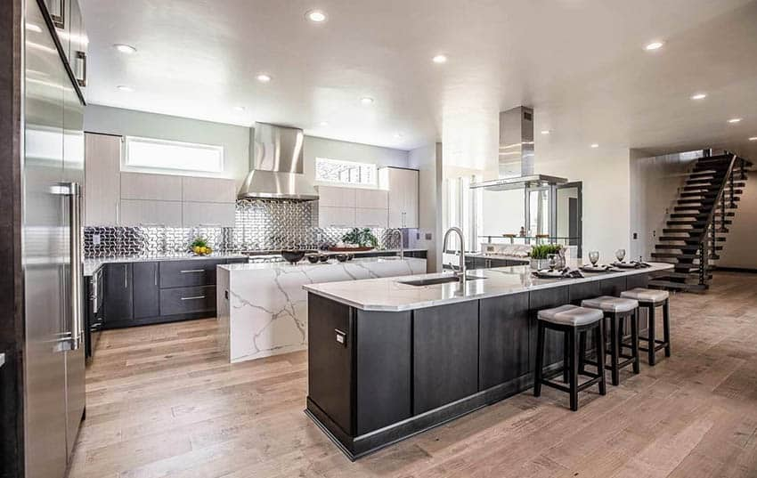 Open concept kitchen with two islands two tone cabinets and waterfall quartz countertop