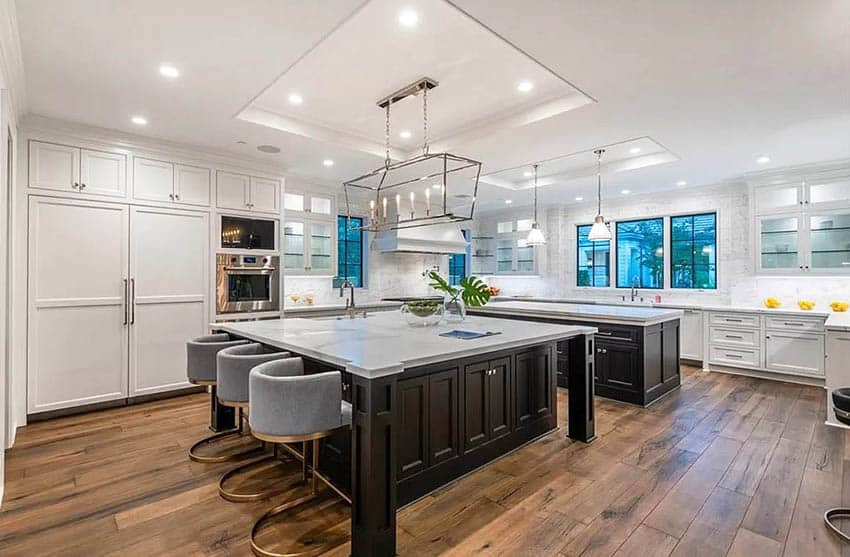 Open concept kitchen with two islands with dark wood base marble countertops and white cabinets