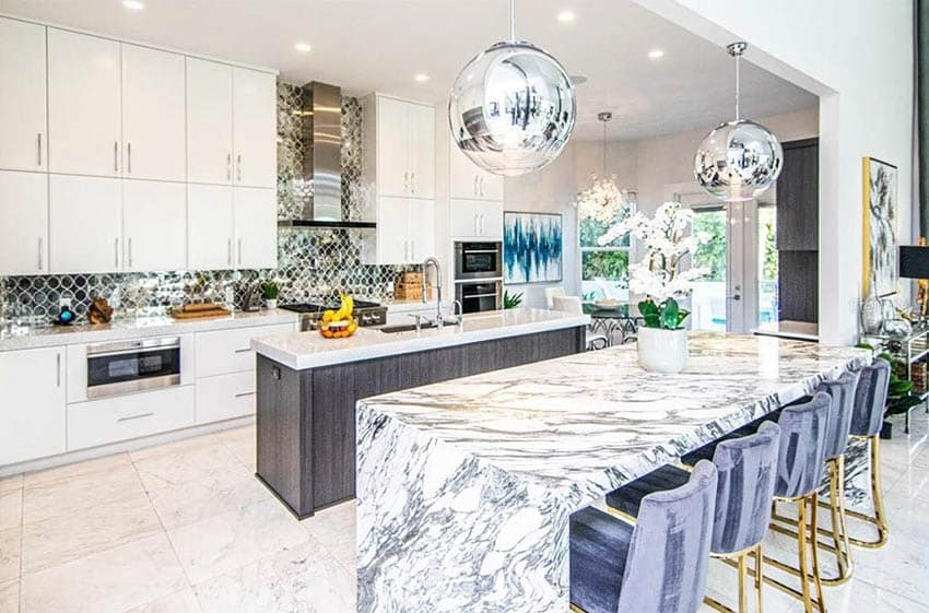 Open concept kitchen with two islands with waterfall countertop and center sink