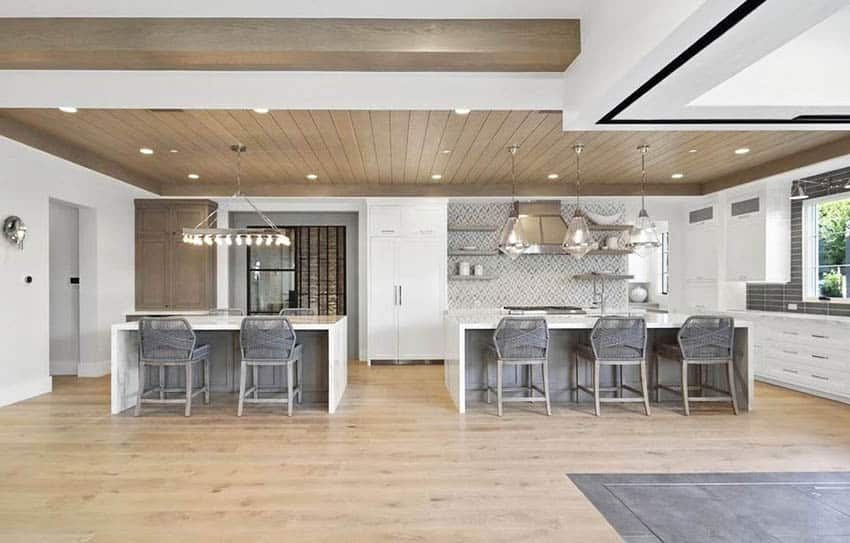 Open concept kitchen with two quartz waterfall counter islands white cabinets wood plank ceiling