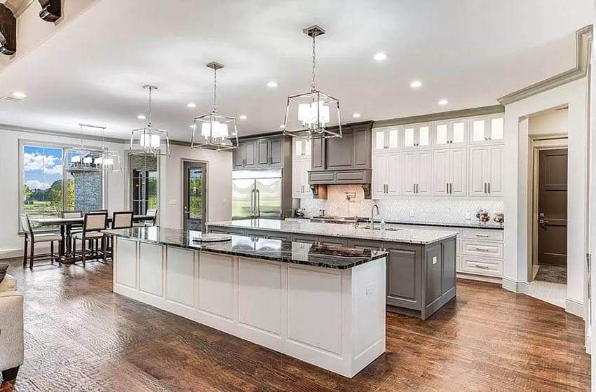 Open layout kitchen with two long islands contrasting quartz countertops two tone cabinets
