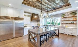 Open plan kitchen with large gray quartz island white cabinets wood tray ceiling