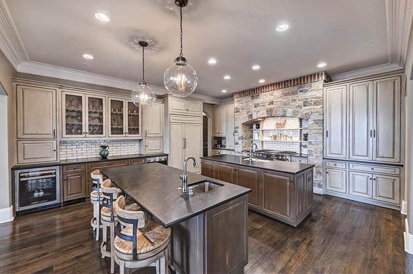 Rustic kitchen with two islands dark cabinets soapstone countertops distressed wood upper cabinets