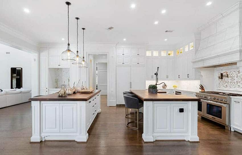Traditional kitchen with two islands butcher block counters white cabinets wood flooring