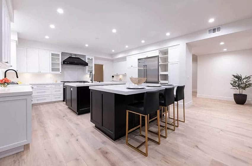 U shaped contemporary kitchen with two islands with black cabinets and white main cabinets