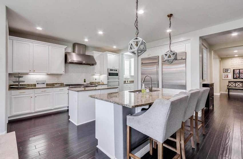 U shaped kitchen with two islands beige granite countertops white cabinets globe pendant lights