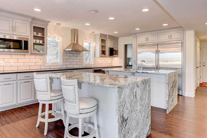 White cabinet kitchen with two islands black and white quartz countertops