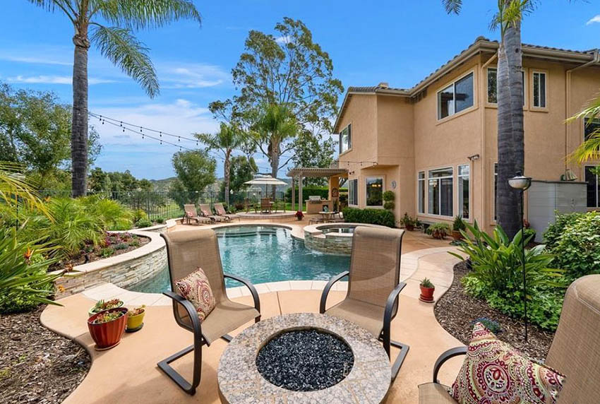 Backyard with granite fire pit and swimming pool