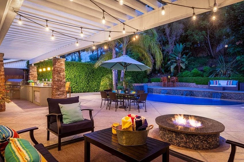 Backyard with granite top fire pit and pool with string lights