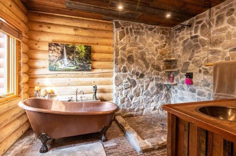 Claw foot copper tub in rustic bathroom