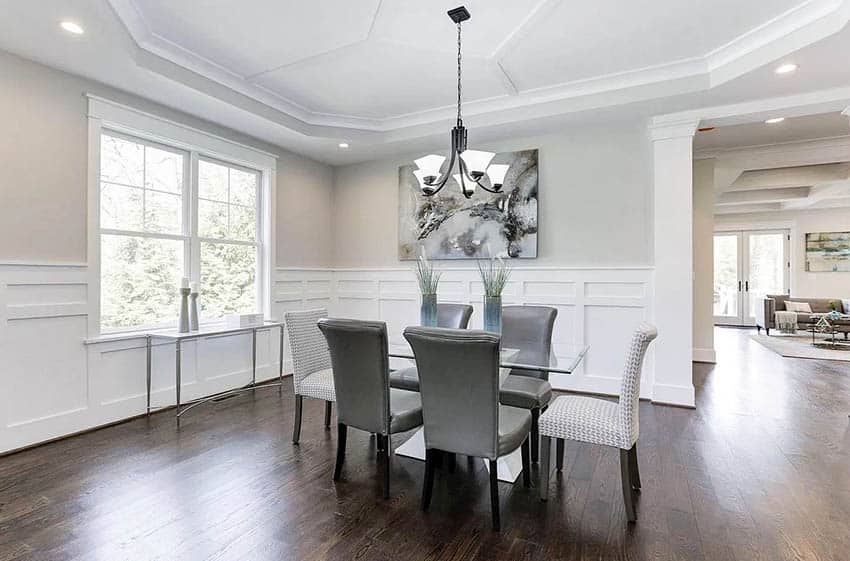 Contemporary dining room with table centerpieces, tray ceiling and white wainscoting