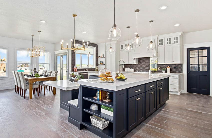 Contemporary kitchen with two black cabinet islands, white main cabinets and wood flooring
