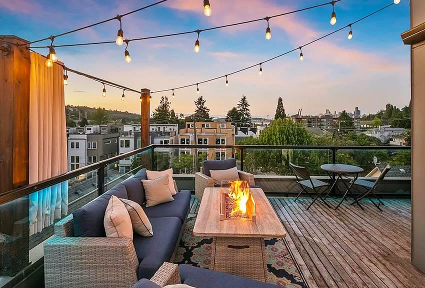 Contemporary rooftop deck with wood flooring, outdoor couch, hanging lights and glass railings