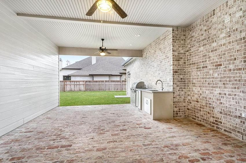 Covered patio with brick floor and outdoor kitchen