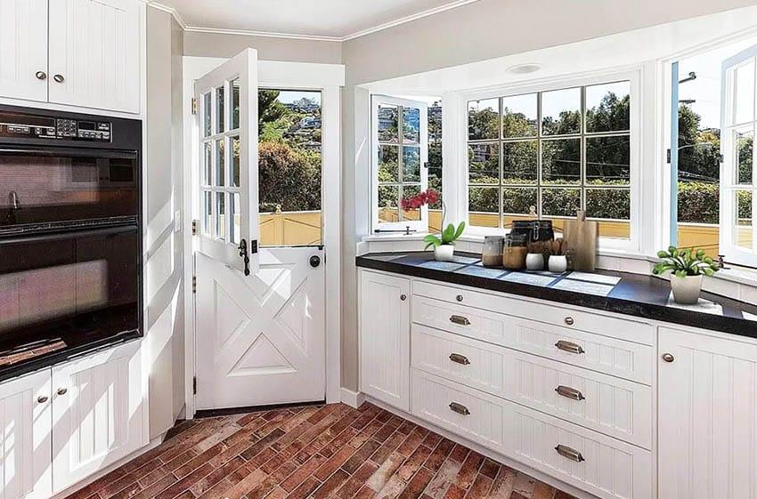 Farmhouse kitchen with dutch door bay window white cabinets