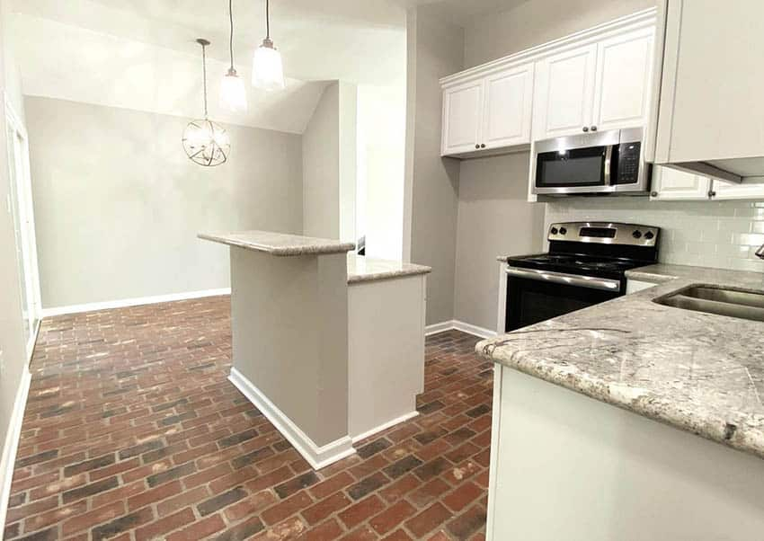 Kitchen with brick floors white cabinets