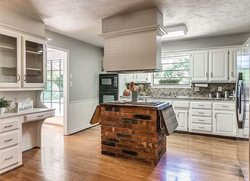 Kitchen with brick island stove top and oven hood