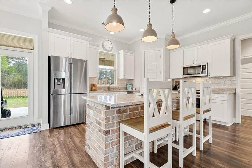 Kitchen with lime washed brick island, white cabinets and wood flooring