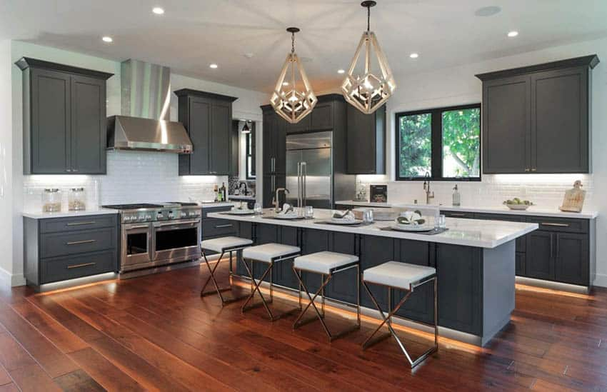 Kitchen with dark gray cabinets island white quartz counters and teak flooring