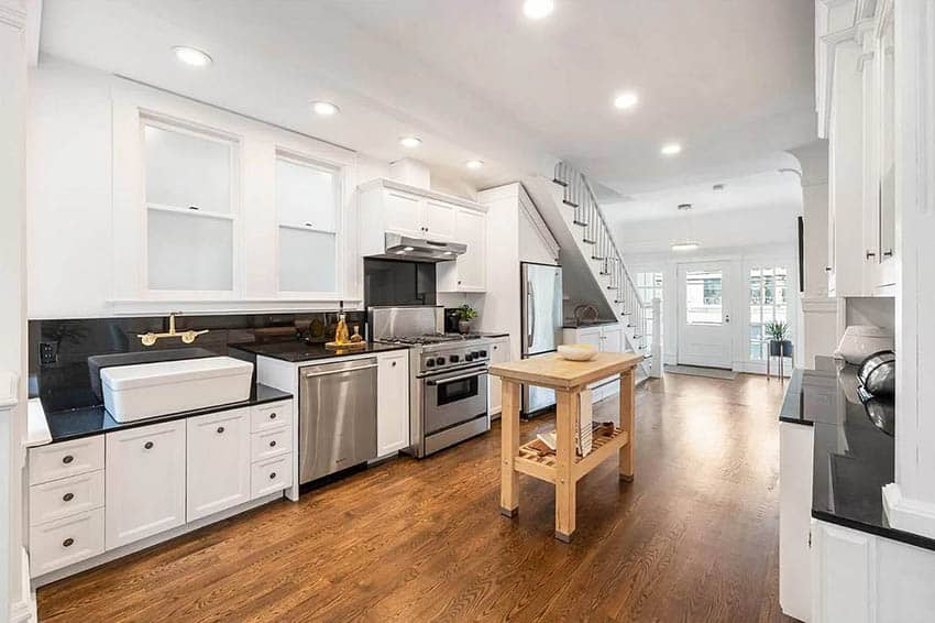 Kitchen with storage below staircase and portable wood island