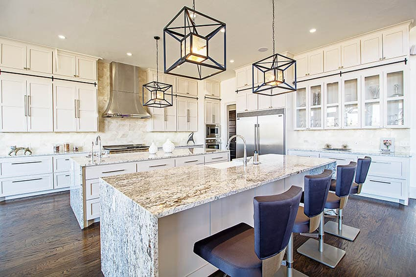 Kitchen with two islands with waterfall granite countertops white cabinets