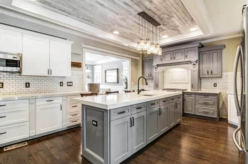 Kitchen with two tone cabinets white gray island with storage wood accent ceiling