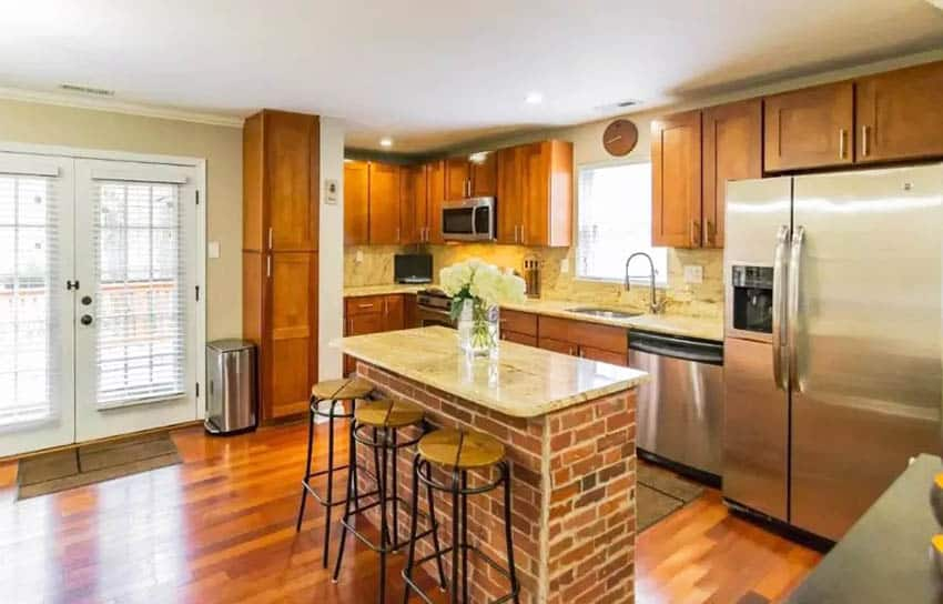 L shaped kitchen with brick island wood cabinets