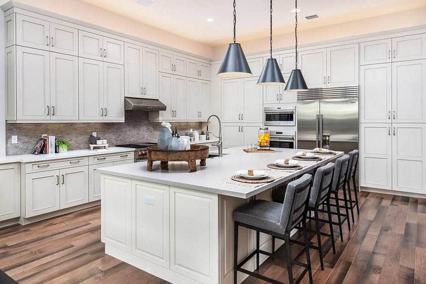 Large kitchen with dining island quartz countertops off white cabinets