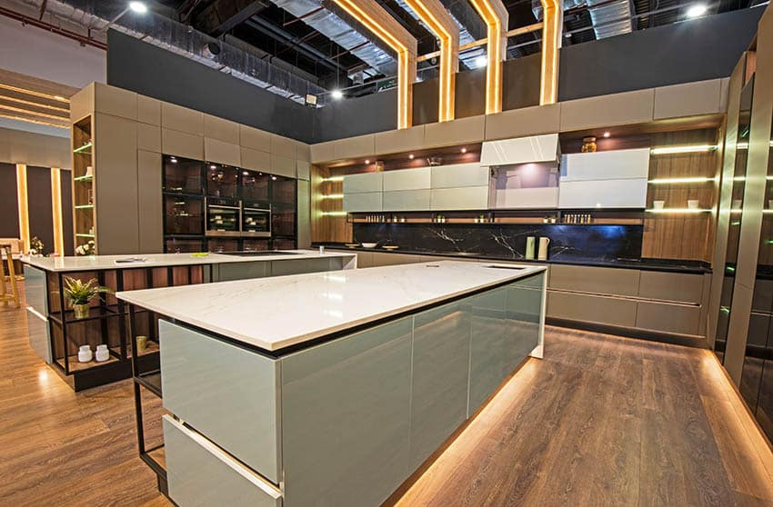 Large modern kitchen with two long islands white corian countertops gray and beige cabinets