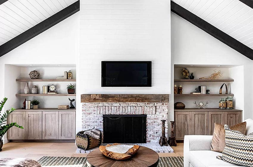 Living room with coffee table centerpiece decor brick fireplace wood mantle and built in shelving
