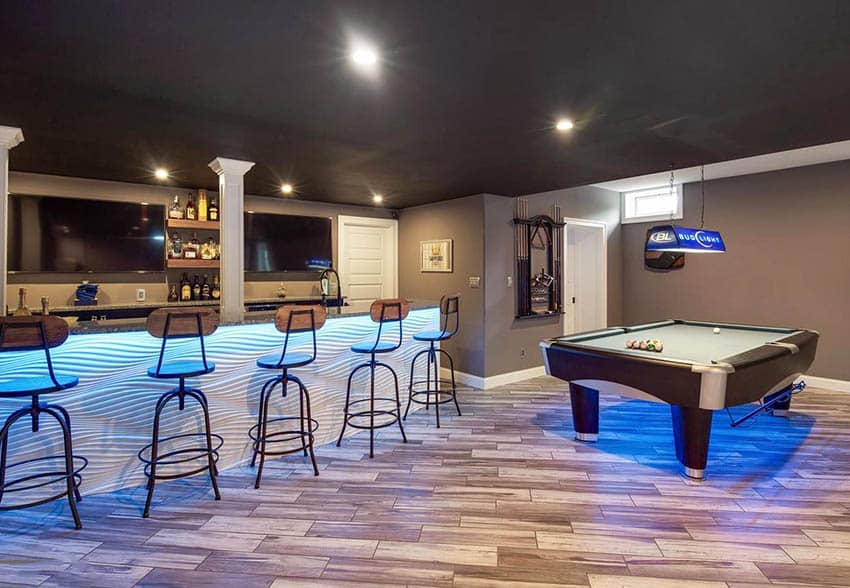 Modern basement game room with home bar and wood plank flooring