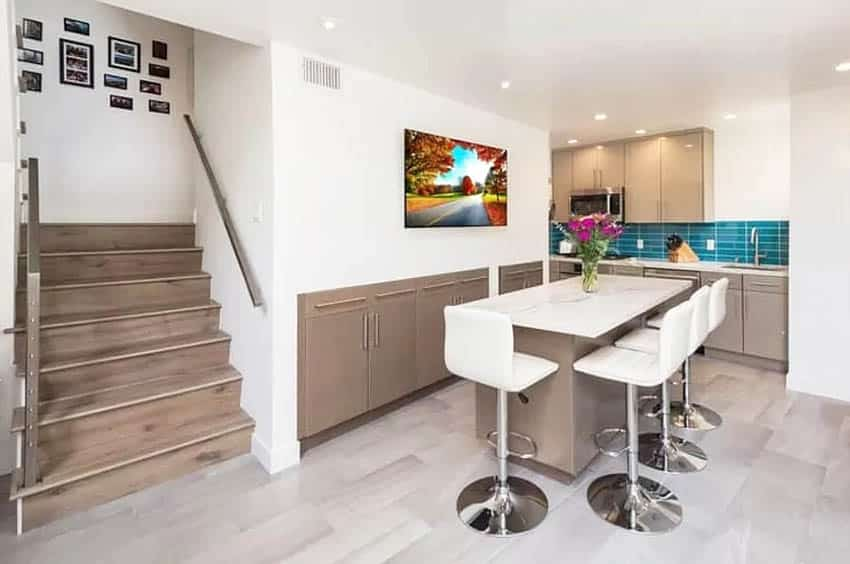 Modern basement kitchen with recessed wall cabinet storage and island with bar stools