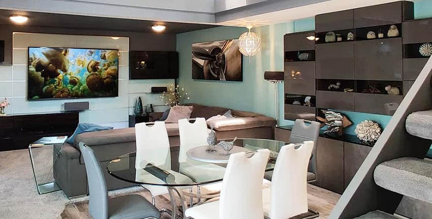 Modern basement living room with teal walls glossy cabinet storage