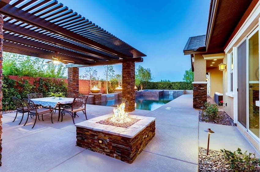 Modern metal pergola with stacked stone support posts=and fire pit