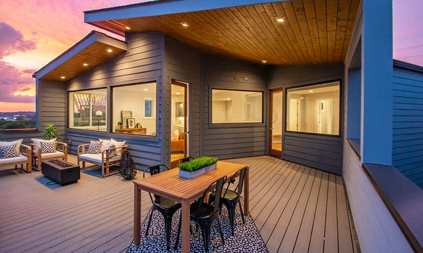 Modern rooftop deck with composite decking outdoor furniture and dining table