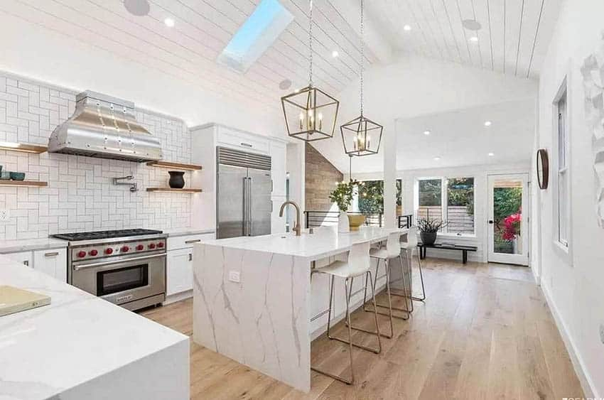 Open island kitchen with skylight shiplap ceiling