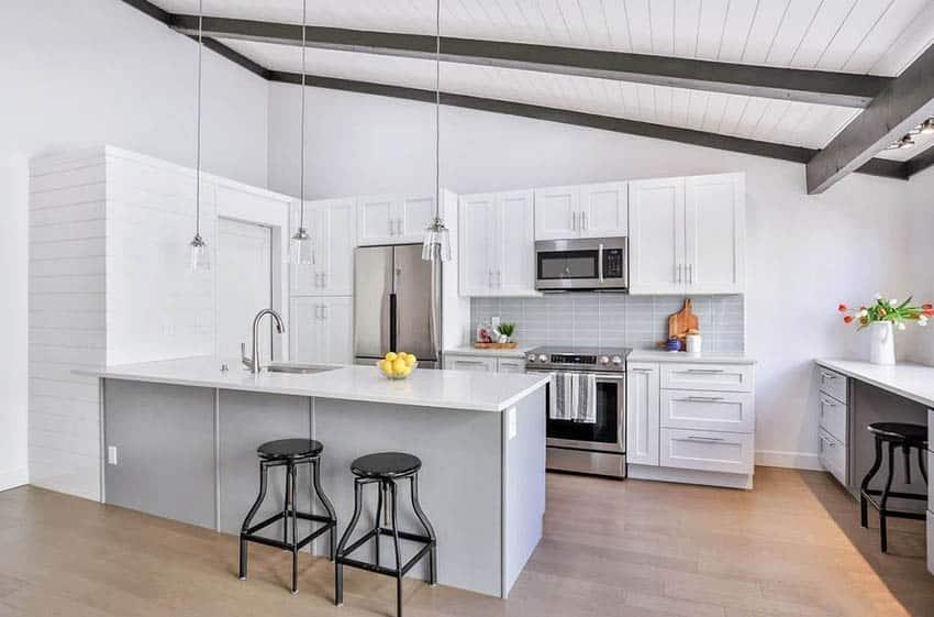 Open kitchen with peninsula white quartz counters white cabinets