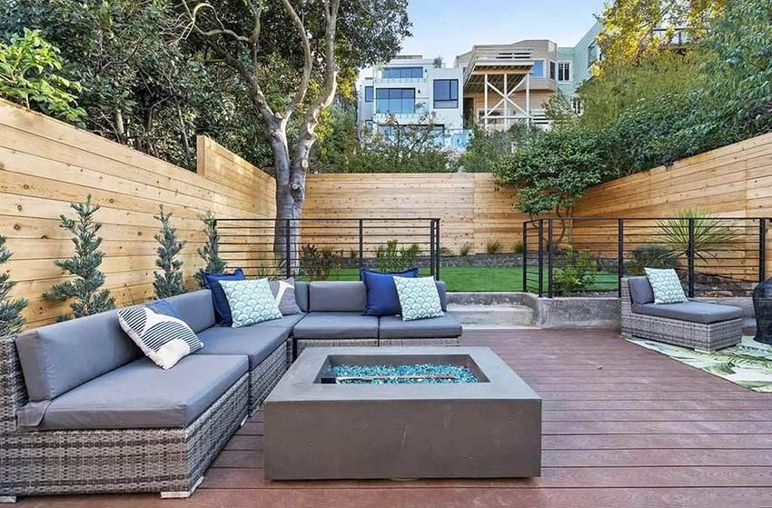 Outdoor living area with sectional couch gas fire pit horizontal wood fencing iron gate