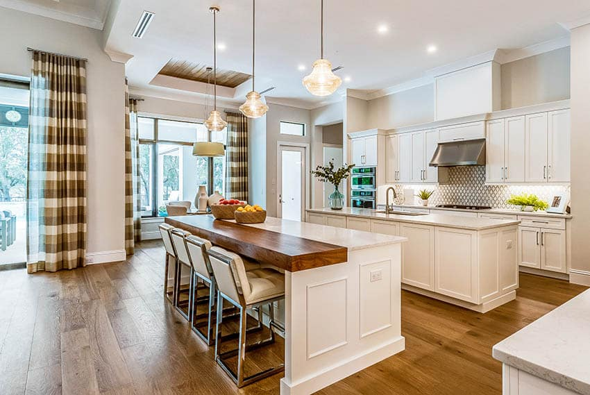 Traditional kitchen with two islands butcher block & quartz counters, white cabinets and wood flooring
