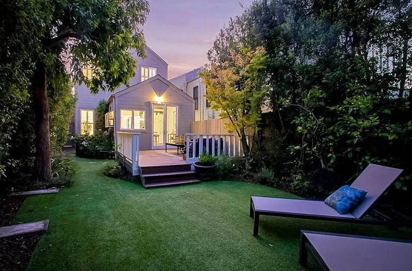 Victorian style house backyard with artificial turf sitting area