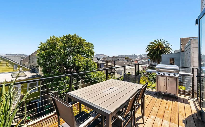 Wood rooftop deck with dining table and barbecue