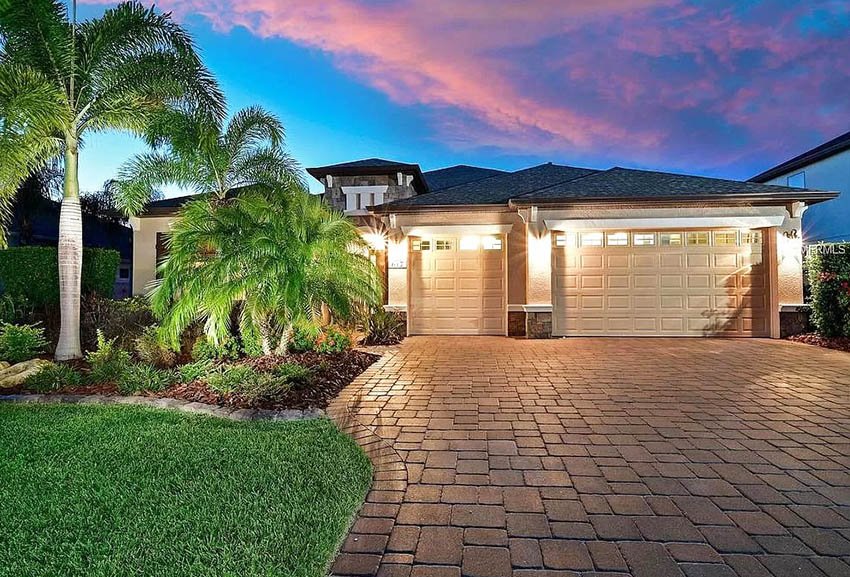 3 car garage house with brick paver driveway