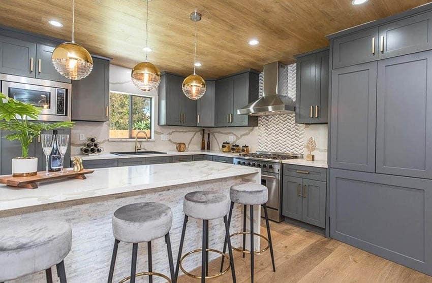 Beautiful kitchen with dark gray cabinets gold accent hardware quartz countertops and backsplash