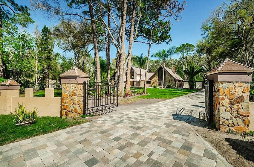 Brick paver driveway with gate entry to home