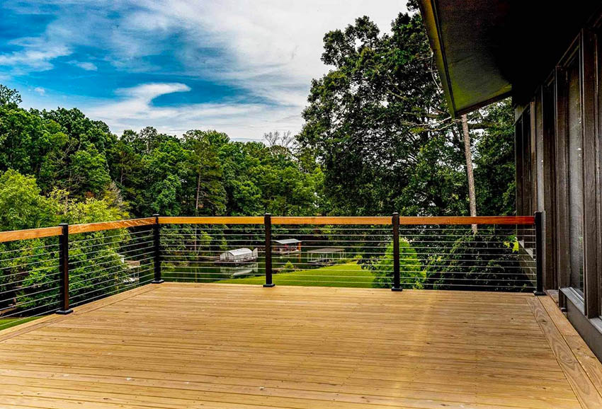 Contemporary deck railing with wood top rail metal posts and cable supports